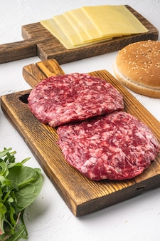 Set di cotolette di carne macinata di manzo, su sfondo di pietra bianca