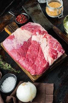 Ombelico di manzo, set di carne di petto di manzo crudo, con ingredienti per fumare barbecue, pastrami, cura, su vecchio tavolo di legno scuro