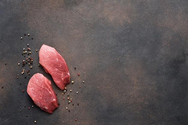 Bistecca di manzo su uno sfondo concreto. vista dall'alto di carne cruda