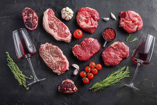 Tagli di bistecca di manzo, rotolo di mandrino, filetto di manzo e bistecca con la lama superiore con erbe aromatiche, condimento e bicchiere di vino rosso sul tavolo nero, vista dall'alto.