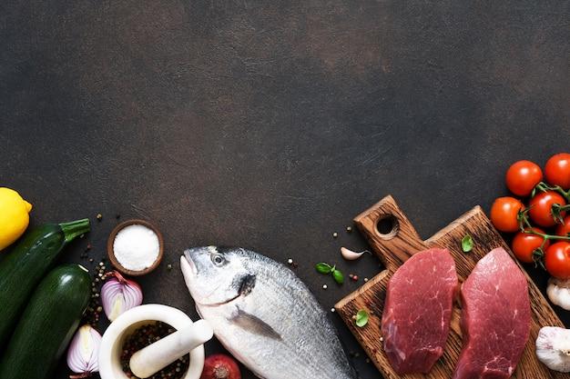 Bistecca di manzo e pesce dorado con spezie e aglio su uno sfondo concreto.