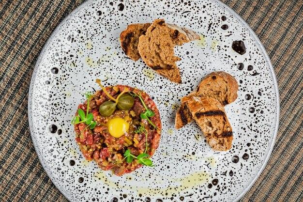 Tartare di manzo con tuorlo d'uovo di quaglia e capperi in cima, servito con crostini di pane alla griglia, su un piatto bianco, vista dall'alto