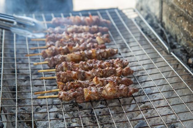 Pinze per bistecca di manzo in acciaio alla griglia con fiamme.
