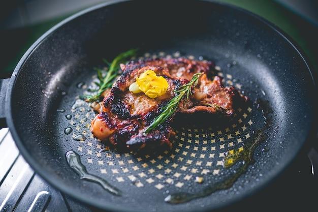 Bistecca di manzo con rosmarino, aglio, sale e pepe all'interno di una padella di ferro