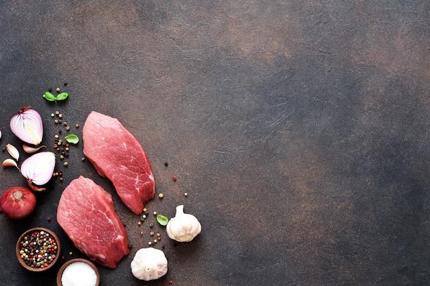 Bistecca di manzo con spezie e aglio su uno sfondo concreto.