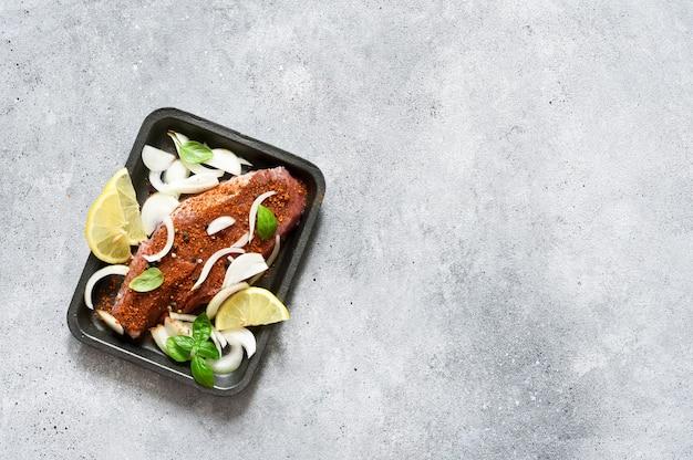 Bistecca di manzo con spezie, cipolle e limone in un vassoio. carne marinata alla griglia.