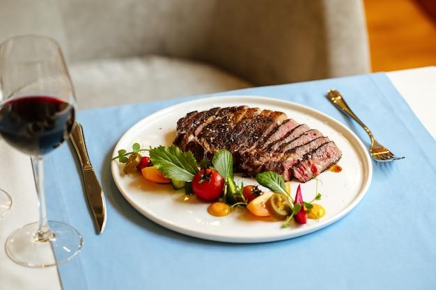 Bistecca di manzo con insalata di verdure e vino sul tavolo blu