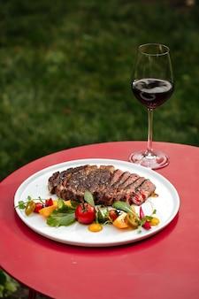 Bistecca di manzo con insalata di verdure e vino sulla tavola rossa