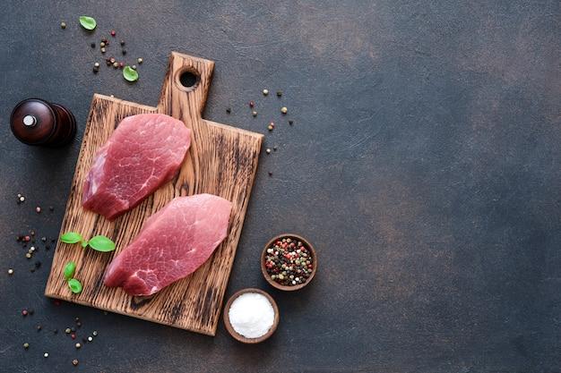 Bistecca di manzo su una tavola di legno con spezie su uno sfondo concreto.