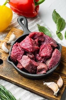 Spezzatino di manzo preparato per la cottura del goulash set con peperone dolce, in padella in ghisa, su superficie di pietra bianca