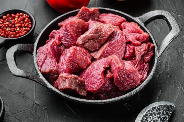 Set di ingredienti crudi di stufato di manzo, in padella in ghisa, sul tavolo di pietra nera