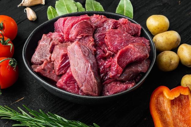 Ingredienti crudi di stufato di manzo con peperone dolce e gratinati sulla tavola di legno nero