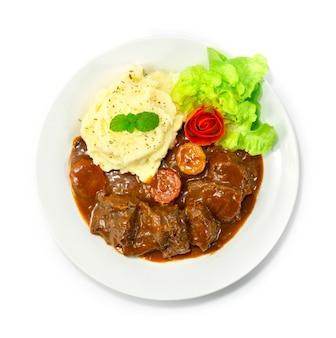 Spezzatino di manzo in salsa al vino rosso purè di patate servito delizioso piatto principale cibo europeo decorazione in stile verdure intagliate vista dall'alto