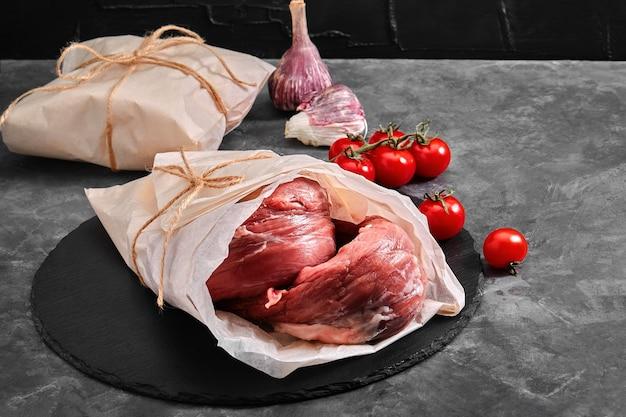 Filetto di manzo di carne cruda. foto per un negozio con prodotti naturali. consegna del cibo, sfondo grigio. copie dello spazio.