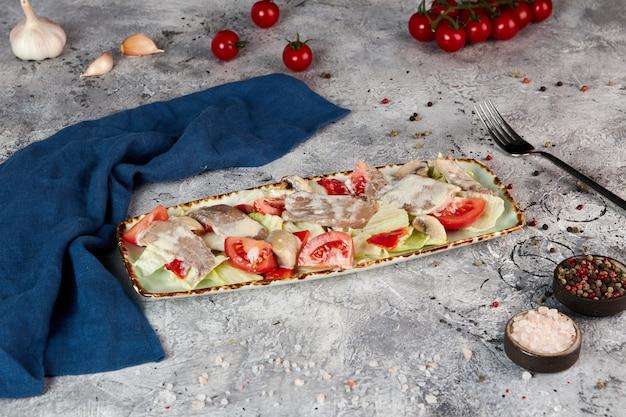 Lingua di manzo insalata con verdure e salsa cremosa, sfondo grigio