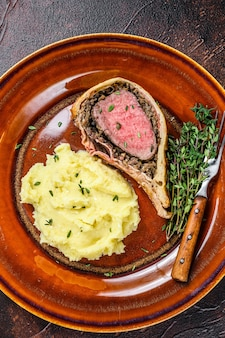 Pasta alla wellington di manzo con patate frullate su un piatto rustico