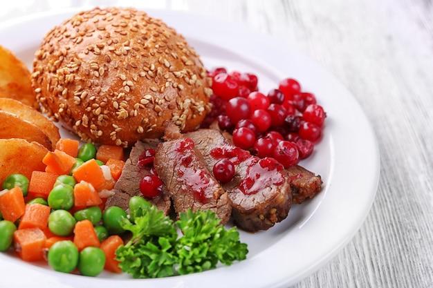 Manzo con salsa di mirtilli rossi, fette di patate arrosto, verdure e panino sul piatto, sulla tavola di legno di colore