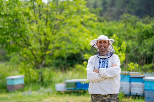 Apicoltore in apiario al giorno d'estate. uomo che lavora in apiario. apicoltura. concetto di apicoltura.