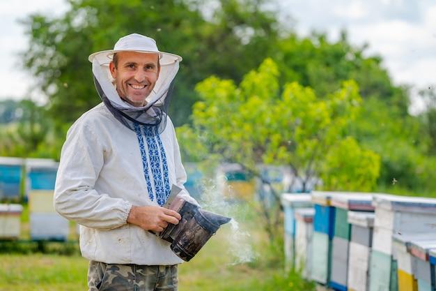Apicoltore in apiario al giorno d'estate. uomo che lavora in apiario con beesmoker. apicoltura. concetto di apicoltura.