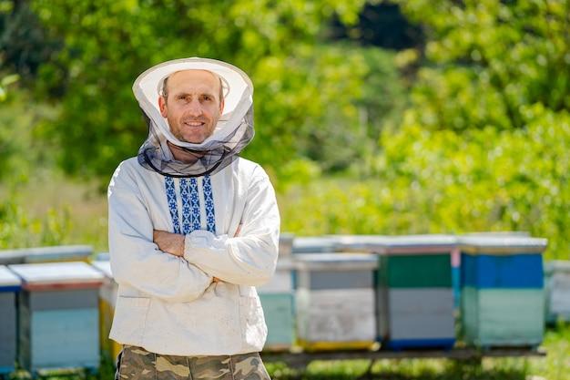 Apicoltore in abiti da lavoro protettivi. sfondo di alveari in apiario. lavora sugli apiari in primavera.