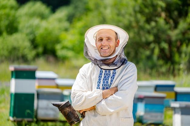 L'apicoltore si trova con le mani incrociate vicino all'apiario. apicoltura. apiario.