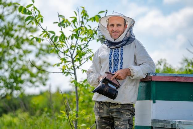 L'apicoltore sta con l'apicoltore vicino all'apiario. apicoltura. apiario.