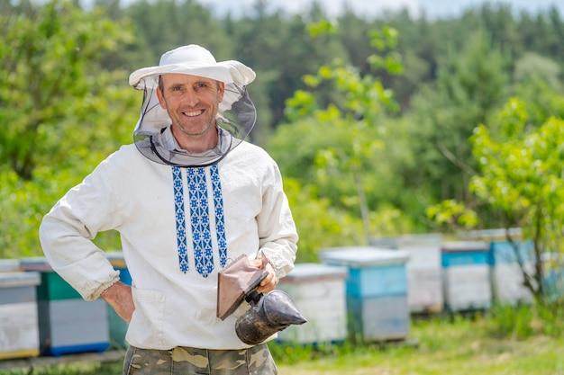 L'apicoltore con un fumatore in mano vicino a un alveare