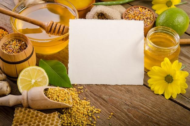 Prodotti di apicoltura con limoni su un tavolo di legno con scheda vuota