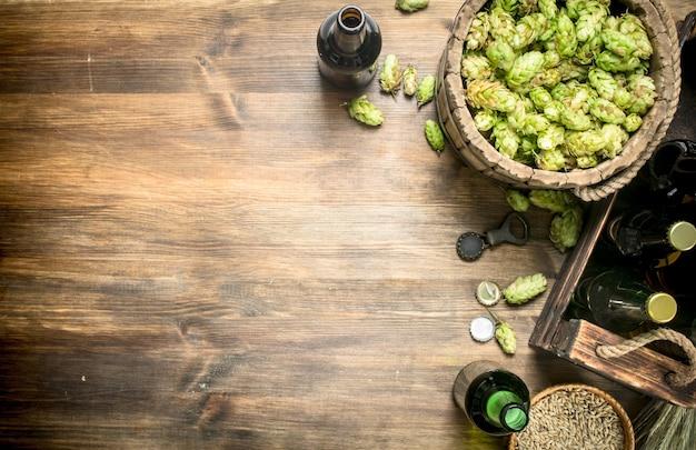 Sfondo di birra birra in bottiglie e ingredienti su un tavolo di legno