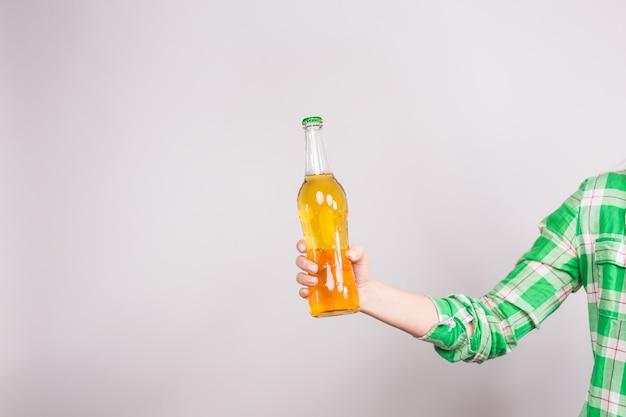 Bottiglia di birra in mano su sfondo bianco.