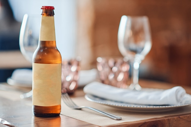 Bottiglia di birra con etichetta gialla sul tavolo con piatto e vetro nel ristorante
