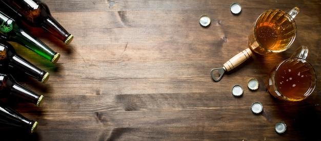 Birra in bottiglie e boccali di vetro. sulla tavola di legno