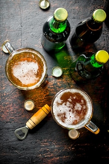 Birra in bottiglie e bicchieri. sulla tavola rustica