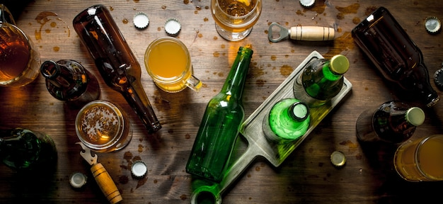 Birra in bottiglie e bicchieri. sullo sfondo di legno