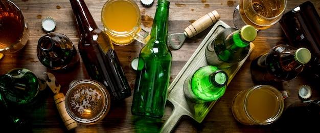 Birra in bottiglie e bicchieri. sulla superficie in legno