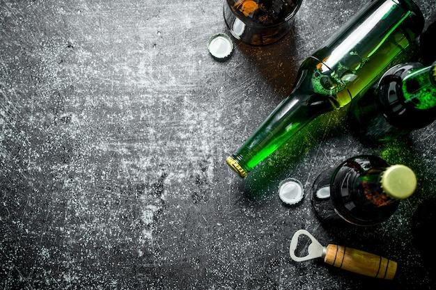 Bottiglie di birra e un apriscatole. su fondo rustico scuro
