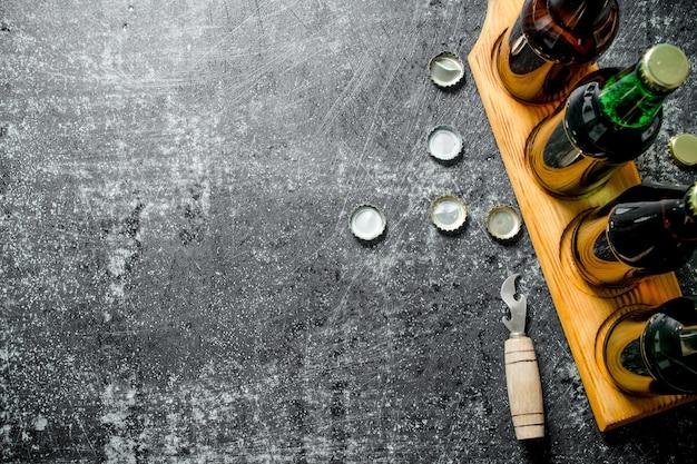 Bottiglie di birra su un supporto e un apri. sulla superficie rustica nera