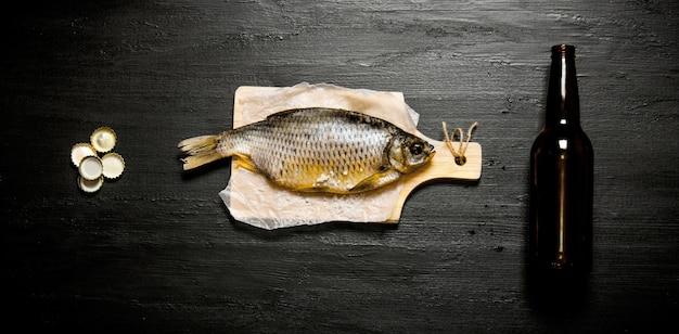 Il concetto di birra. pesce essiccato e bottiglia di birra sul bordo nero. vista dall'alto