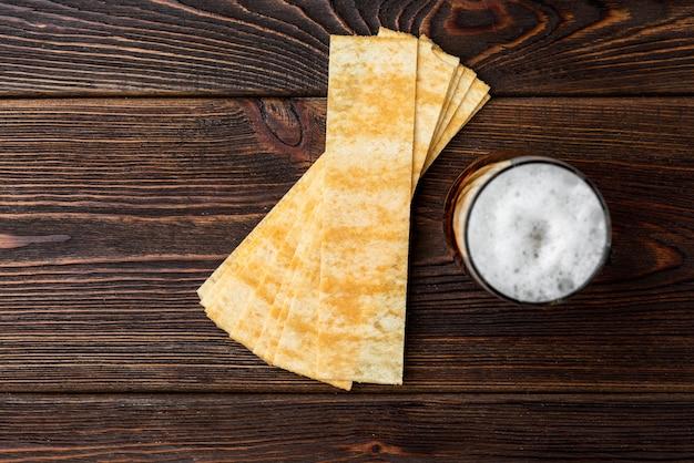 Birra e patatine su fondo di legno scuro.
