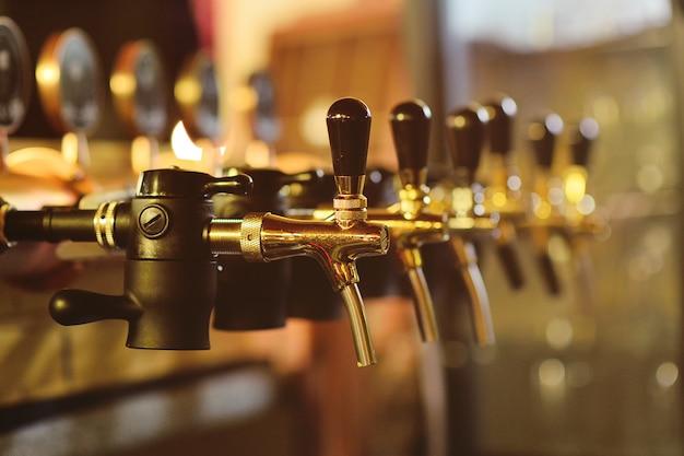 Primo piano del rubinetto della birra contro una barra nel pub
