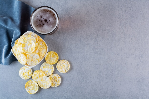 Bicchiere da birra e ciotola di patatine su un pezzo di tessuto, sulla superficie del marmo