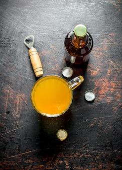 Birra in una tazza di vetro e una bottiglia. sul tavolo rustico scuro