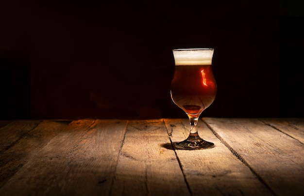 Bicchiere da birra su uno sfondo di legno scuro con spazio di copia