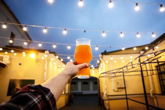 Birra in un bicchiere in mano illuminata da lanterne