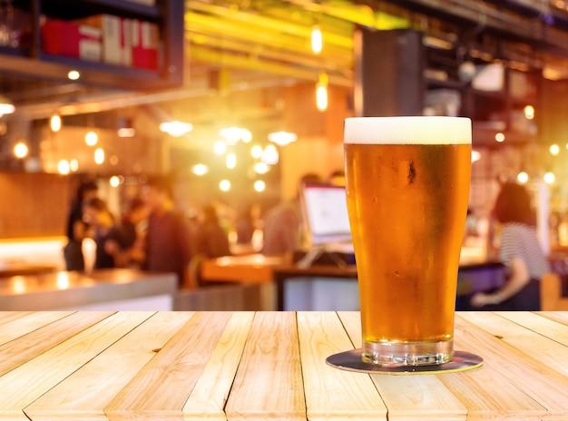 Birra nel bicchiere su tavola di legno marrone chiaro sul davanti con bar e ristorante sfocati sfocati.