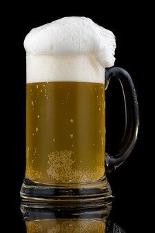 Birra in un bicchiere e schiuma bianca