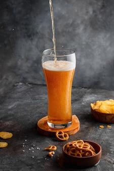 Birra nel bicchiere con bollicine scottate con patatine e pretzel sul tavolo scuro