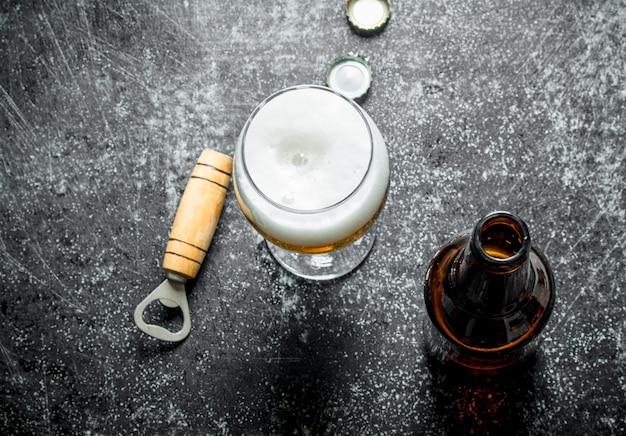 Birra in un bicchiere con apriscatole.