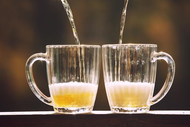 Birra in bicchieri grandi e luce di vetro dorato con il primo piano di schiuma