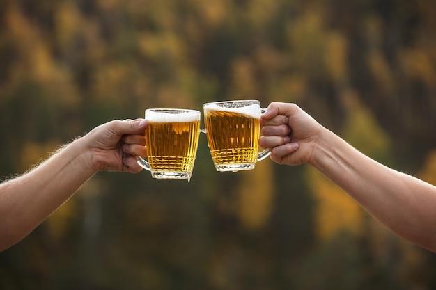 Birra in bicchieri grandi e luce di vetro dorata con schiuma e mani di close-up amici